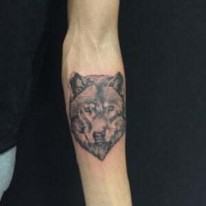 Tatuaje de lobo blanco y negro en el brazo.